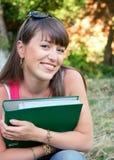 Giovane ragazza sorridente con un dispositivo di piegatura Immagine Stock
