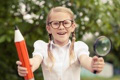 Giovane ragazza sorridente della scuola in un uniforme scolastico contro un albero dentro Fotografia Stock Libera da Diritti