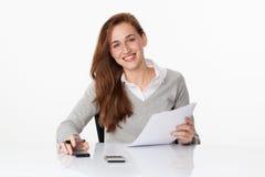 Giovane ragazza sorridente di affari che lavora o che studia al suo scrittorio Immagine Stock Libera da Diritti