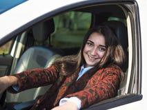 Giovane ragazza sorridente graziosa che si siede dietro la ruota di un'automobile Fotografie Stock