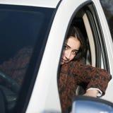 Giovane ragazza sorridente graziosa che si siede dietro la ruota di un'automobile Immagine Stock Libera da Diritti