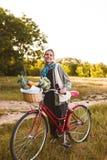 Giovane ragazza sorridente sulla bicicletta rossa con i wildflowers ed i frutti dentro immagini stock