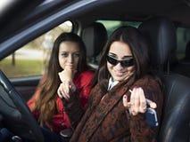 Giovane ragazza sorridente sveglia due che si siede in un'automobile immagini stock