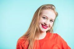Giovane ragazza sorridente sveglia su fondo blu immagini stock libere da diritti