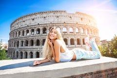 Giovane ragazza sorridente in vacanza a Roma con il Colosseum nei precedenti immagini stock