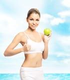 Giovane, ragazza sportiva, adatta e bella con la mela isolata sopra immagini stock