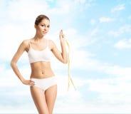 Giovane, ragazza sportiva, adatta e bella con nastro adesivo di misurazione Fotografia Stock