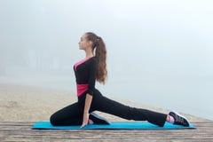 Giovane ragazza sportiva che allunga durante l'allenamento di addestramento all'aperto Fotografia Stock Libera da Diritti