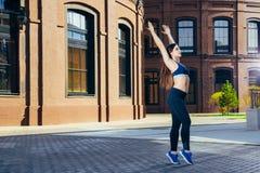 Giovane ragazza sportiva che allunga, preparando per risolvere, scaldandosi dopo o prima della forma fisica su aria fresca Immagine Stock Libera da Diritti