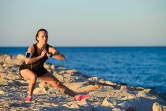 Giovane ragazza sportiva che allunga sulla spiaggia Fotografia Stock Libera da Diritti