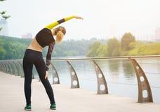 Giovane ragazza sportiva che fa allungamento nel parco della città Immagini Stock Libere da Diritti