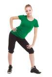 Giovane ragazza sportiva che fa allungando esercizio isolato Fotografia Stock