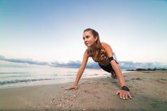 Giovane ragazza sportiva che fa esercizio della plancia sulla spiaggia all'alba Fotografia Stock