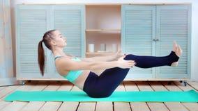 Giovane ragazza sportiva che fa gli esercizi per forma fisica della stampa e la foto a figura intera di pratica di yoga archivi video