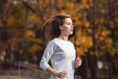 Giovane ragazza sportiva che pareggia nel parco della città al giorno di autunno Immagini Stock Libere da Diritti