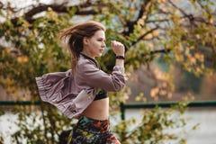 Giovane ragazza sportiva che pareggia nel parco della città al giorno di autunno Fotografia Stock