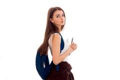 Giovane ragazza stanca degli studenti con lo zaino blu sulla spalla e cartelle per i taccuini in mani che esaminano la macchina f Immagini Stock