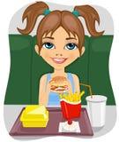 Giovane ragazza sveglia che mangia hamburger con le patate fritte ed il coke Immagine Stock