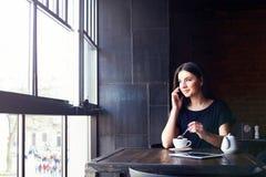 Giovane ragazza sveglia che parla sul telefono in caffè Immagini Stock Libere da Diritti