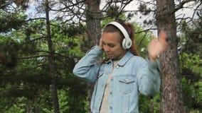 Giovane ragazza sveglia in cuffie che ascolta la musica sul telefono cellulare archivi video