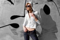 Giovane ragazza sveglia del brunette vicino ad un graffito Immagine Stock