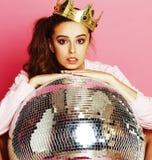Giovane ragazza sveglia della discoteca su fondo rosa con la palla e la corona della discoteca immagine stock