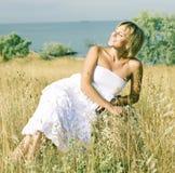Giovane ragazza sveglia di estate su erba gialla fuori del sorridere di rilassamento immagine stock