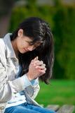 Giovane ragazza teenager biraziale che prega all'aperto Fotografia Stock