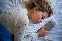 Giovane ragazza teenager che dorme e che tiene telefono cellulare immagine stock libera da diritti