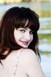 Giovane ragazza teenager che esamina spalla che sorride al fiume Fotografia Stock