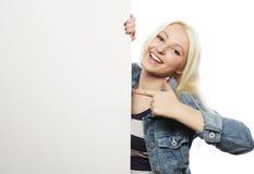 Giovane ragazza teenager che indica sul bordo in bianco Priorità bassa bianca Immagine Stock