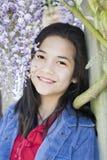 Giovane ragazza teenager che si leva in piedi sotto le viti di glicine Immagine Stock