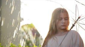 Giovane ragazza triste castana con la condizione lunga dei capelli in pioggia di versamento senza ombrello Primo piano, rallentat archivi video
