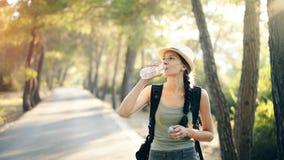 Giovane ragazza turistica attraente che rinfresca dall'acqua potabile dopo il viaggio di viaggiatore con zaino e sacco a pelo fotografia stock