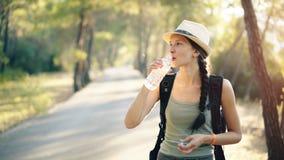 Giovane ragazza turistica attraente che rinfresca dall'acqua potabile dopo il viaggio di viaggiatore con zaino e sacco a pelo immagine stock