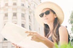 Giovane ragazza turistica attraente che sta sulla vecchia via con la mappa e lo sguardo della città intorno fotografie stock