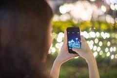 Giovane ragazza turistica che prende una foto improvvisa del colpo della luce notturna della città Fotografia Stock