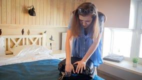 Giovane ragazza turistica che prova a chiudere valigia piena nella camera di albergo immagini stock