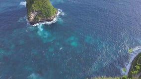 Giovane ragazza turistica della corsa mista che sta sull'orlo della scogliera con le armi stese contro l'oceano blu stupefacente  stock footage