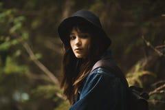 Giovane ragazza turistica sola del cutie che si siede sulla pietra sulla riva del fiume in montagne in terreno selvaggio e nella  fotografia stock
