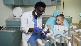 Giovane ragazzino africano di insegnamento del dentista come pulire i denti sul modello di plastica archivi video