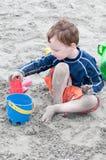 Giovane ragazzino che gioca con la sabbia ed il castello di sabbia di costruzione alla spiaggia vicino al mare Immagine Stock
