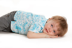 Giovane ragazzino che si trova sul pavimento isolato su fondo bianco immagine stock