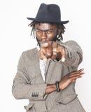 Giovane ragazzo afroamericano bello in cappello alla moda dei pantaloni a vita bassa che gesturing emozionale isolato sul sorride Fotografia Stock Libera da Diritti