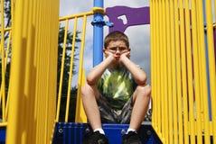 Giovane ragazzo al campo da giuoco fotografie stock