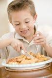 Giovane ragazzo all'interno che mangia i pesci ed i chip Immagine Stock