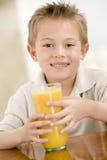 Giovane ragazzo all'interno con il succo di arancia Fotografia Stock Libera da Diritti