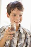 Giovane ragazzo all'interno sorridere dell'acqua potabile Immagini Stock