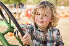 Giovane ragazzo allegro che gioca su un vecchio trattore fuori Immagini Stock Libere da Diritti