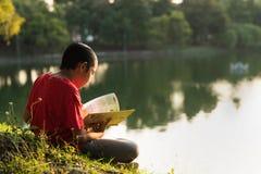 Giovane ragazzo asiatico in camicia rossa che legge un libro Immagini Stock Libere da Diritti